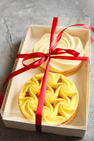 Delicious mini tarts yellow and white with nuts and custard in the gift box. Assortment of delicious and colorful dessert, lemon curd tart, cream chocolate tart made by chef