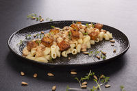 Delicious pasta with chickpeas, fried tofu and fresh herbs on black plate.