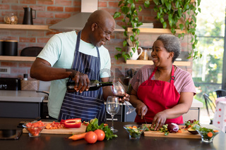 Happy african american senior couple cooking together in kitchen, drinking wine