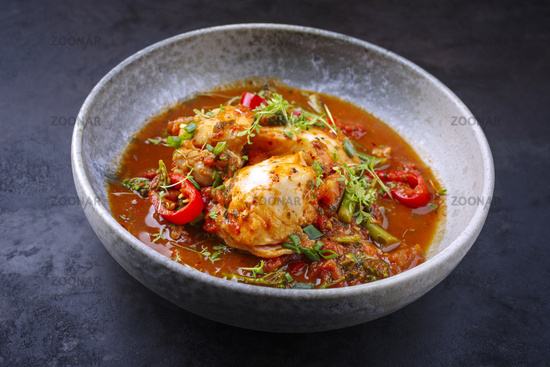 Modern style traditional Spanish seafood zarzuela de pescado with fish served in red sauce as close-up in a design bowl