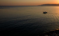 Aerial drone view of fishing boat sailing in the sea at sunrise. Latsi Paphos Cyprus