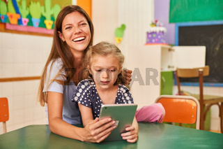 Glückliche Tagesmutter und Mädchen am Tablet Computer
