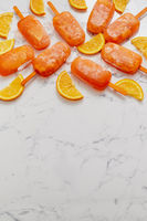 Homemade frozen popsicles made with oragnic fresh oranges placed with ice cubes on marble table