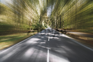 empty two-lane country road through woodland with motion blur