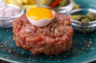 Steak Tartar mit offenem Ei auf Holz