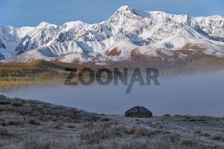 Shepherd's house ail Altai lake Dzhangyskol on mountain plateau Eshtykel. Morning fog over water. Altai, Russia