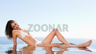Smiling woman enjoys sunbathing on pool edge