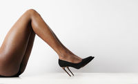 Cropped image of female legs with black high heels shoes. Isolated.