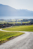 Path to Austrian mountain village with foggy valley background during fall in Wildermieming, Tirol,