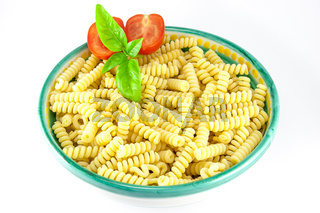 Bowl full of fusilli pasta with tomatoes and basil