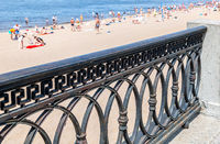 Cast iron trellis on the embankment against the background of a sandy beach