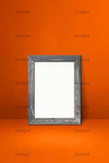 Wooden picture frame leaning on an orange wall