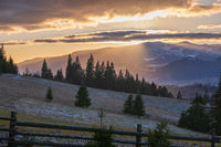 Picturesque sunset above late autumn mountain countryside.  Ukraine, Carpathian Mountains. Peaceful traveling, seasonal, nature and countryside beauty concept scene.