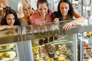 Women friends looking at cakes in cafe