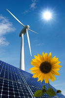 Solar modules, wind turbine and sunflower in front of a sunny sky