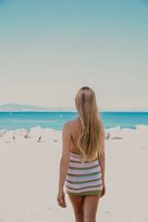 Vertical image of blonde long-haired woman walking on the beach in sunny day.