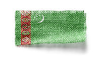 Turkmenistan flag on a piece of cloth on a white background