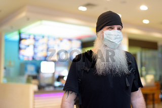 Mature bearded hipster man as backpacker with mask thinking inside the mall