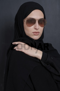 Young muslim businesswoman in traditional clothes or abaya and sunglasses posing in front of black chalkboard