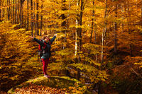 Woman is standing on the big stone in the autumn forest