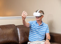 Senior adult man playing a game on a modern VR headset