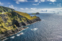 Tall Kerry Cliffs and a view on silhouette of Skellig Michael island in a distance
