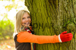 Smiling teenager girl embracing tree autumn woods