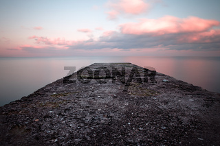 Calm sea sunset with a jetty