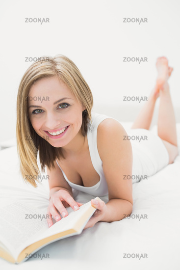 Portrait of young woman reading book in bed