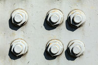 Six large nuts and bolts on gray steel plate of rail bridge, lit by bright sun. Abstract industrial background.