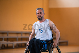 a photo of a war veteran playing basketball with a team in a modern sports arena. The concept of sport for people with disabilities