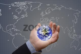 Hand hält Erde vor Weltkarte