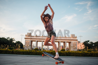 Young sporty woman riding on the longboard skateboard in the park