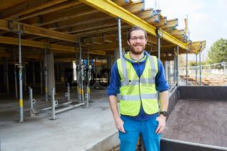 Junger Mann als Handwerker Lehrling auf Baustelle