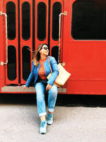 Happy young woman traveler in denim clothes sitting on steps of red travel bus