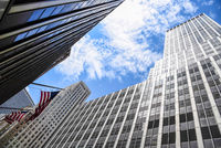 Low angle view of American flag and skyscrapers against sky in New York