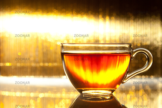 Cup of tea on shiny gold background