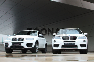 Two white BMW X3 and X6 after rain