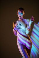 Topless woman illuminated by stripes of neon light
