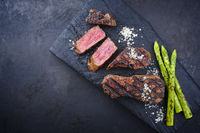 Rustic barbecue dry aged wagyu roast beef steak with green asparagus and salt served as top view on a charred wooden board with copy space left
