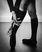 Legs of young ballerina with pointe shoes dancing on a black floor background. Ballet practice. Feet of ballet dancer.