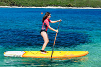 Young active girl on a sup board with a paddle in her hand - shot from the side; calm surface of the sea