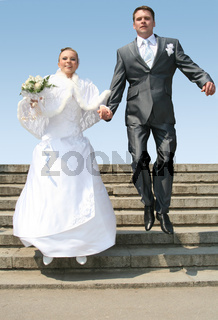 husband and bride jumping against blue sky
