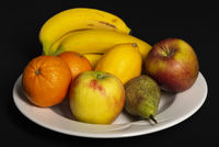 Fruit bowl with bananas, oranges, apples, lemon and pear