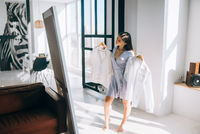 Beautiful girl trying dress in room