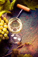 White wine and grapes in vintage setting with bottle opener on kitchen table.