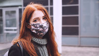 young woman wearing homemade everyday cloth face mask outdoors in city