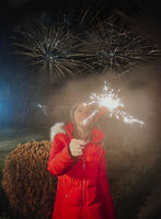 Happy girl holding sparkler while celebrating New Year outdoors in twilight