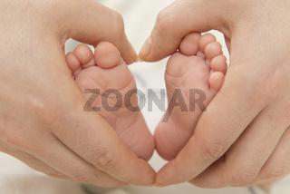Mutterhand zeigt Herz um Babyfüße