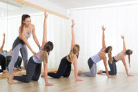 Group of young sporty sexy women in yoga studio, practicing yoga lesson with instructor. Healthy active lifestyle, working out indoors in gym